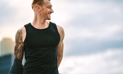 Close up of a smiling fitness man looking away