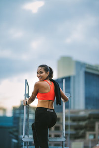 Smiling fitness woman standing on rooftop staircase