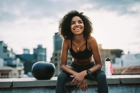 Smiling woman athlete taking a break during workout