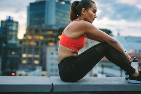 Woman in fitness clothes sitting on rooftop