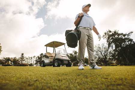 Senior golfer with bag on the golf course