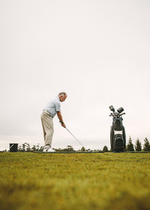 Senior golfer practicing at golf course driving range