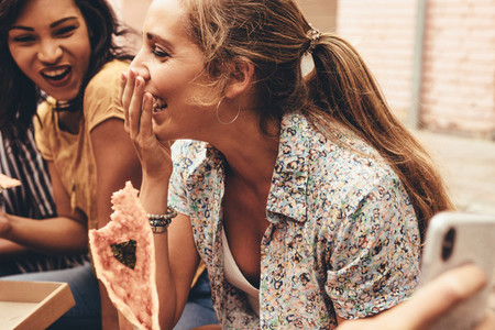 Woman having fun eating pizza with friends