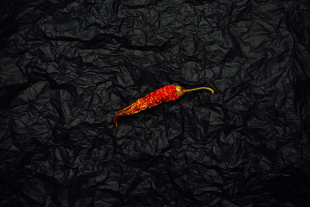 Red hot pepper against a crumpled black background