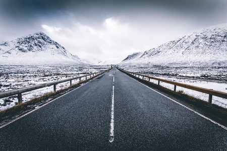Open road winter snow mountain landscape in Glencoe Scotland