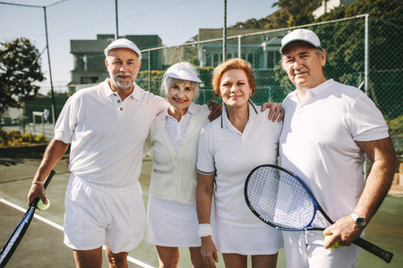Senior men and women standing together on a tennis court