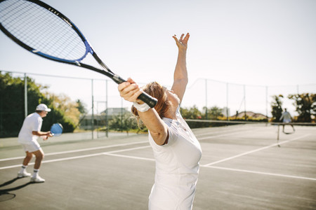 Senior woman making a serve while playing tennis