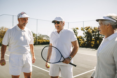 Senior men and a woman standing on a tennis court