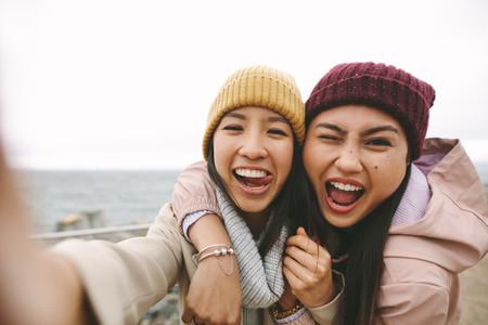 Two asian women friends having fun standing outdoors
