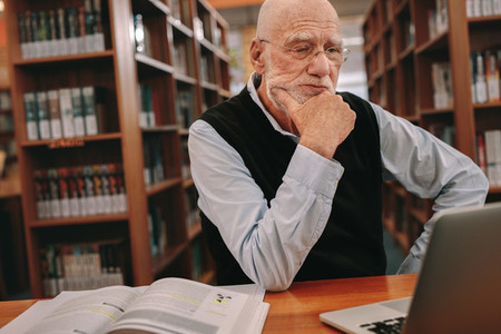 Senior man studying in library