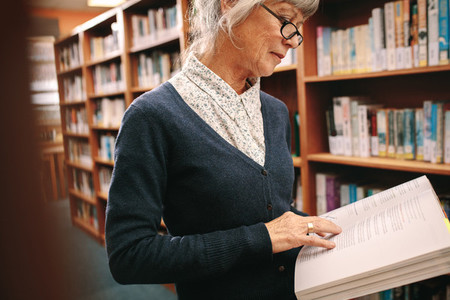 Portrait of a senior woman reading a book in library