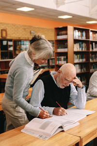 Senior lecturer helping an elderly man in university class