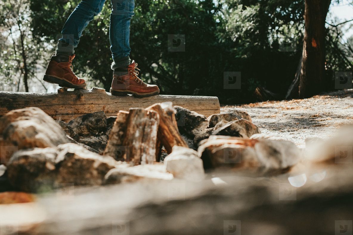 Person walking on log of wood in a forest