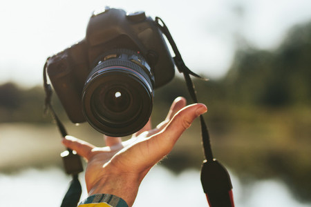 Close up of a hand of man tossing up a dslr camera