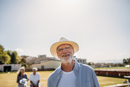 Close up of a senior man standing in a park
