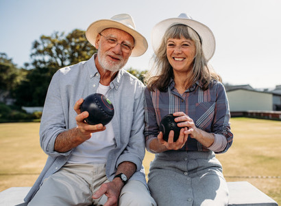 Senior couple sitting in a  park holding boules