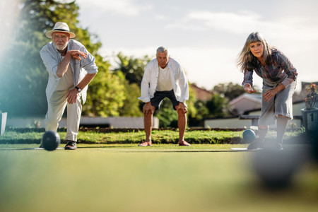 Elderly couple playing boules in a park