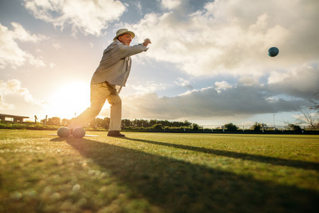 Senior man playing boules in a lawn