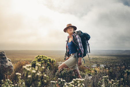 Female hiker enjoying the view standing on a hill