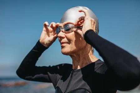 Senior woman getting ready to swim in the sea