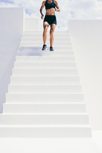Female athlete running down the stairs of a building