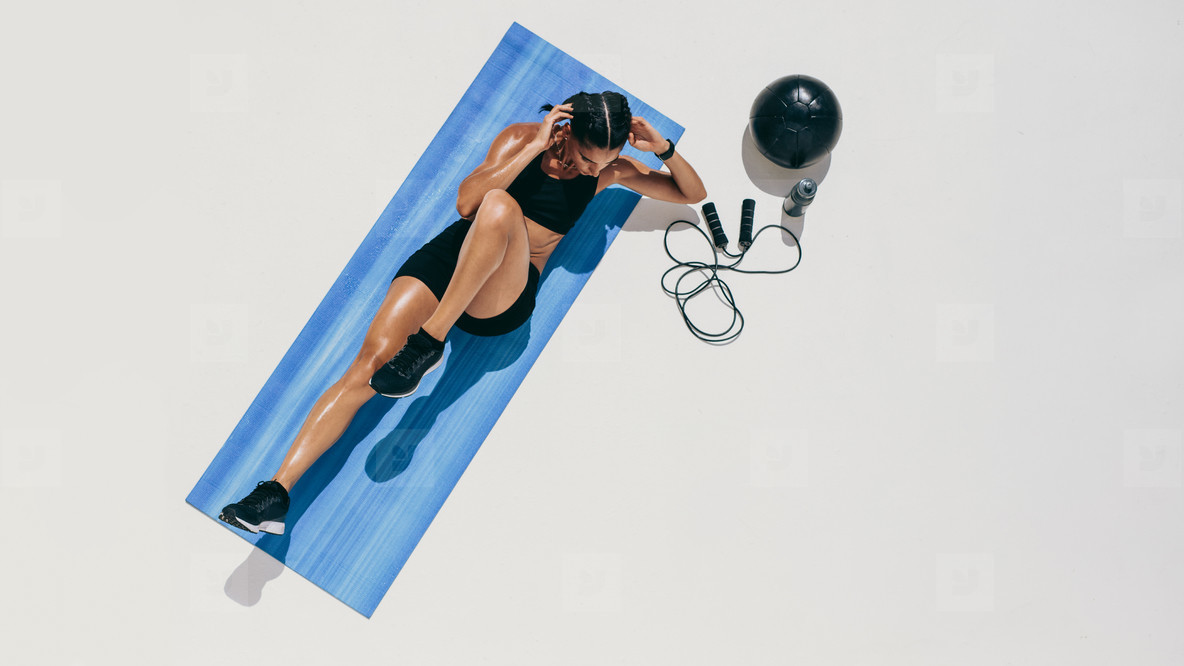 Fitness woman doing workout on a yoga mat