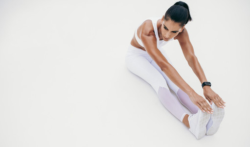 Woman in white fitness clothes doing warm up exercises