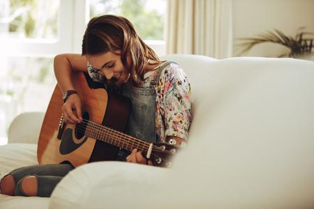 Girl enjoying playing guitar at home