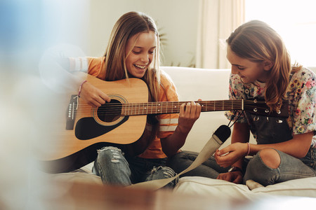 Girls having fun learning guitar