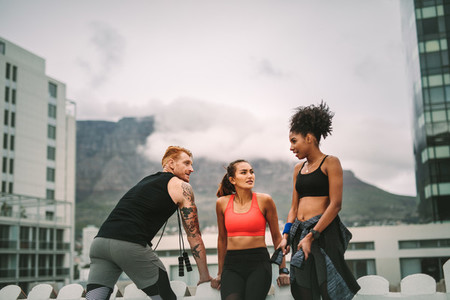 Group of fitness people standing on rooftop after workout
