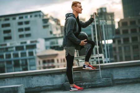 Fitness man standing on rooftop holding a medicine ball