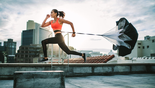 Woman running on rooftop with a resistance parachute