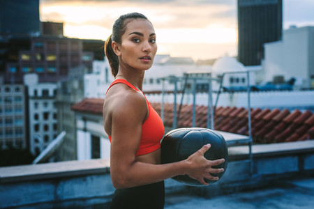 Portrait of a woman standing on rooftop holding a medicine ball