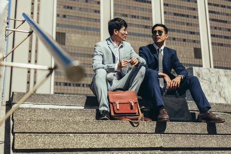 Business partners sitting on the steps outdoors and talking