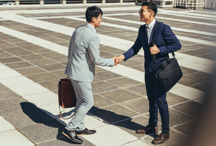 Two businessmen shaking hands outdoors in the city
