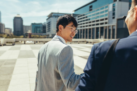 Asian businessmen walking and talking in the city