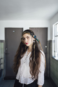 Hippie female standing near window
