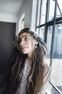Hippie female standing near window