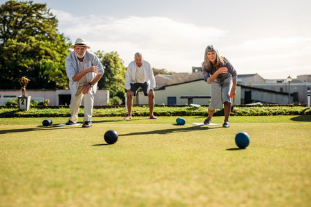 Senior man and woman playing boules in a lawn
