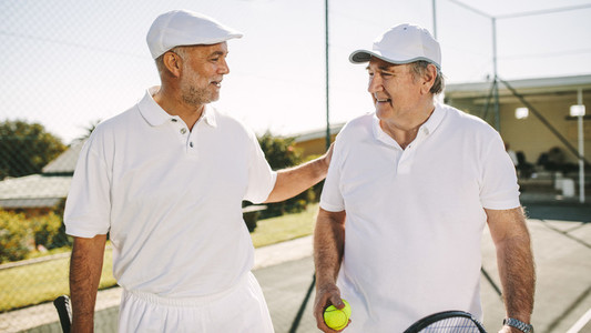 Senior men playing tennis
