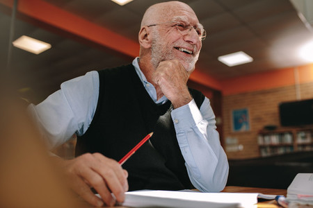Portrait of a smiling senior man sitting in a library