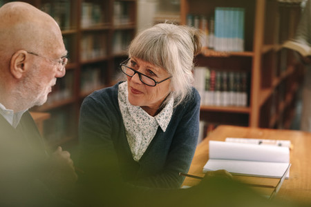 Senior couple interacting with each other sitting in a library