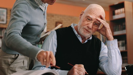 Cropped shot of a female helping a senior man in classroom