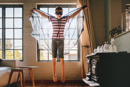 Boy in bat costume at home