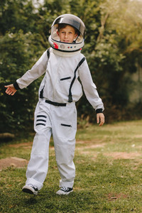 Kid playing in astronaut suit outdoors