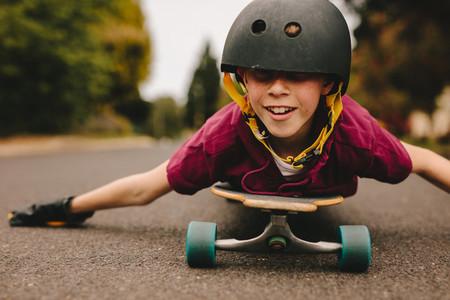 Funny boy with helmet lying on skateboard