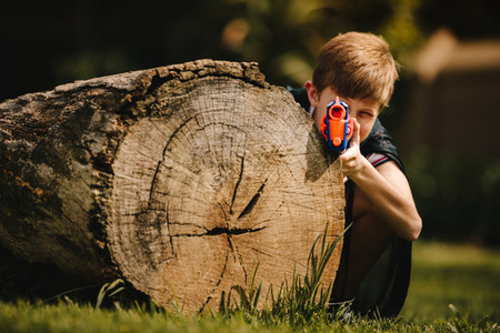 Boy playing with a toy gun outdoors