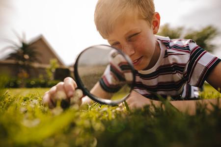 Boy exploring garden with his magnifying glass
