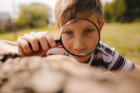 Boy exploring with magnifying glass at the park