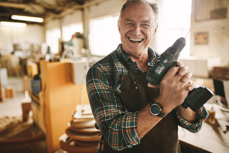 Smiling senior carpenter holding drill machine